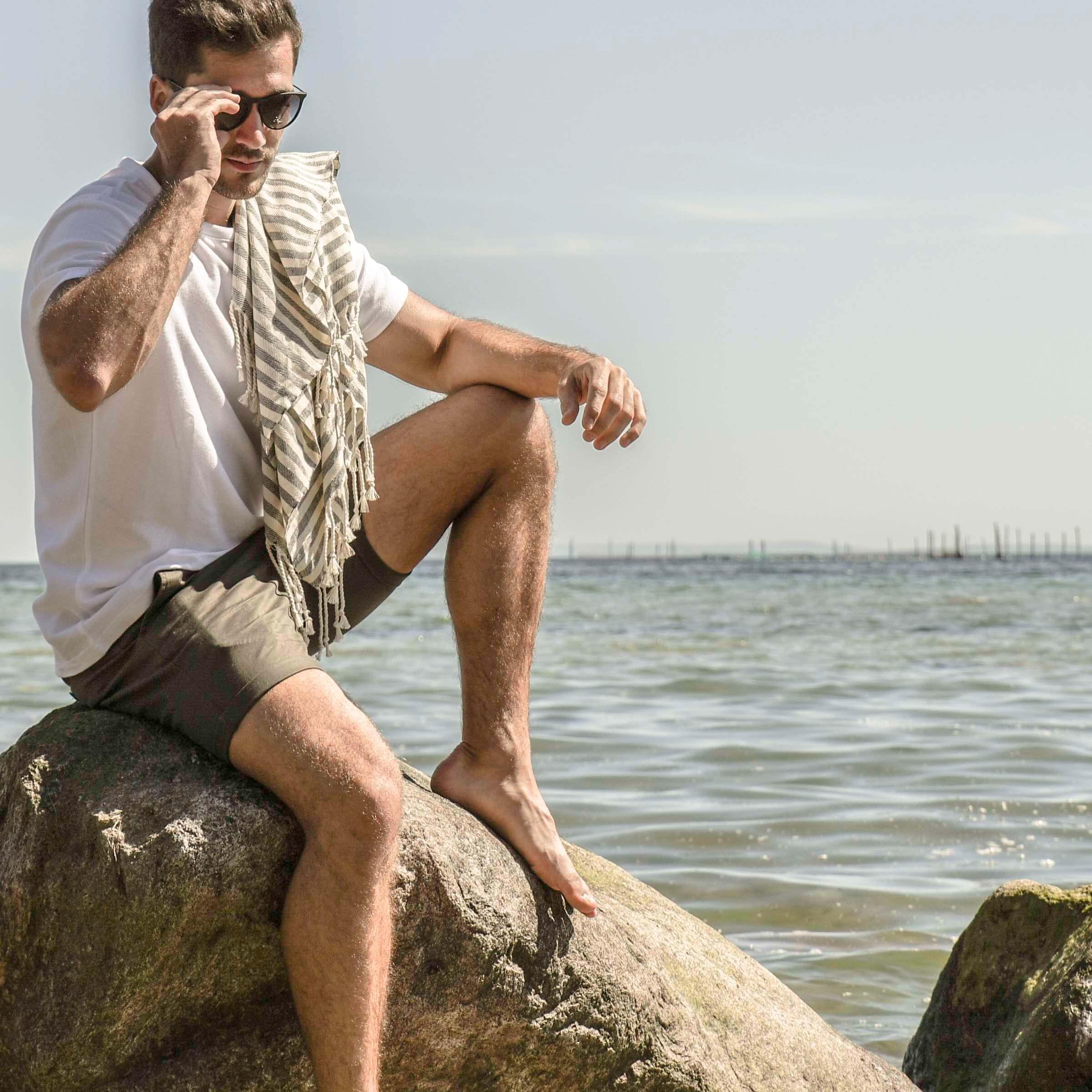 mand med hammam håndklæde over skulderen på solrig strand